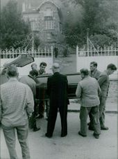 Men taking the coffin out of a funeral car.