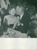 Maurice Chevalier kissing a woman on her cheeks.