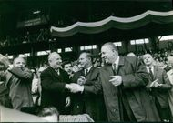 Year ?  A scene of a French Socialist politician Gaston Defferre handshaking and meeting with men in the assembly.