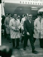 Henry Kissinger with his bodyguard upon arrival at Heathrow Airport