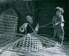 A man with his child plaiting bamboo.