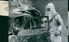 A man wearing a Fire proximity suit standing beside a car on fire.