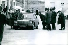 Men standing and gathered, looking in the car.