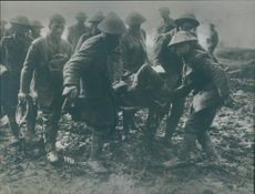 Soldiers helping an injured man during wartime.