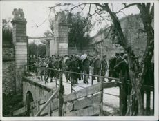 Soldiers and prisoners walking together on the bridge.