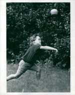 A young boy playing with his ball.