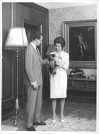 Juan Carlos I caressing the poodle his wife holding.