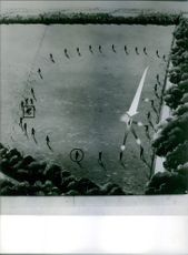 Soldiers standing in circle and firing.