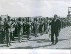 A photo of an Algerian Politician Ferhat Abbas walking in front of soldiers.  July 4 1962