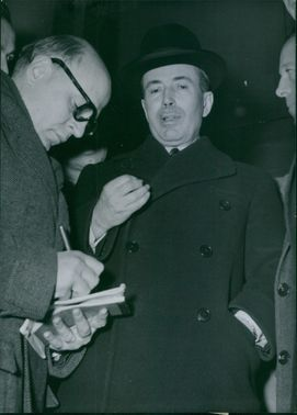 Portrait of  a French conservative politician Antoine Pinay standing with men, while another man writing on his diary.