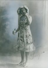 Woman standing and holding a cosmetic bottle.