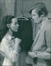 Michael York and a woman staring on each other.