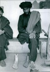 Pakistani handicapped man siting and looking at the artificial foot.
