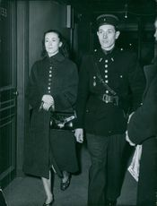 A guard guards the woman while walking together. 1960