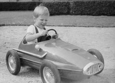 Prince Laurent in a toy car.