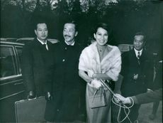 Nguyen Cao Ky walking with his wife, while a press reporter holding and talking, 1968.