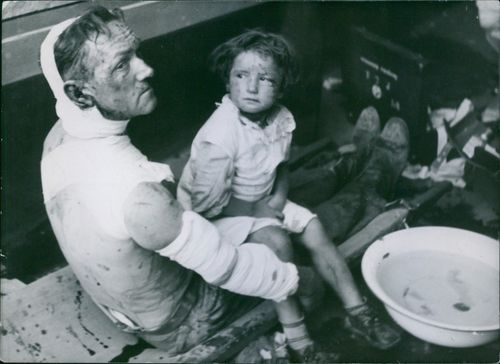 A wounded man sitting with his child and looking towards the camera.