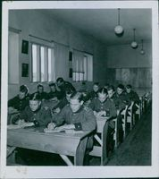 Soldiers in the classroom while writing in the paper during First World War, 1939.