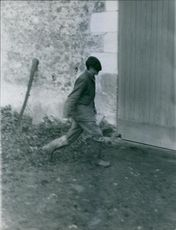 A man in muddy boots and rugged clothes walking fast towards a barn. Photo taken during an investigation of the Michelin murder case. Photo taken on October 24, 1960.