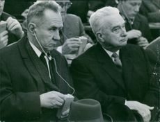 Alexei Nikolayevich Kosygin sitting with other people and listening something from the head phones.