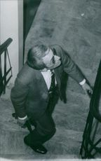A man in suit with a gun, vigilantly walking upstairs,1970.