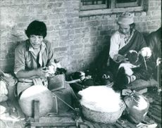 A photo of men sitting, holding a wool and working in Nepal.