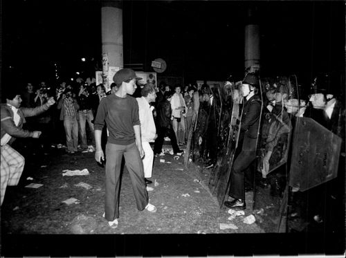 A bunch of young people stand against a wall of policemen when the carnival in Notting Hill ends in fights and insurgency