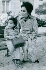Dewi Sukarno siting with child in the garden.