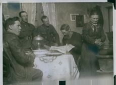 Soldiers looking the woman cooking something during Tyskland war.