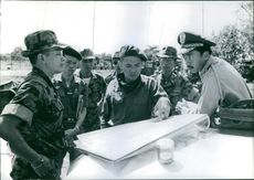 Soldiers discussing and indicating at paper.