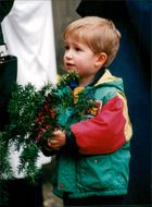 A boy holding a plastic leaves.