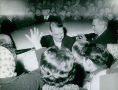 Rene Coty surrounded by people.