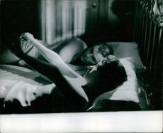 Woman stretching her hands while John Saxon laying down on the bed with her.