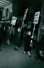 Women marching in street while protesting.