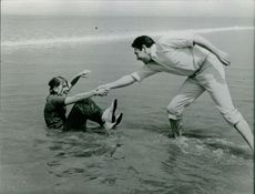 Robert Hossein with a woman having good time on the beach.