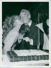 Maurice Chevalier in a party and a woman kissing on his cheek.