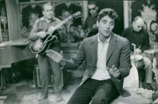 Sacha Distel singing, band in the background.