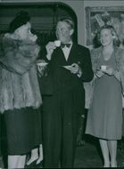 Maurice Chevalier drinking tea with women.