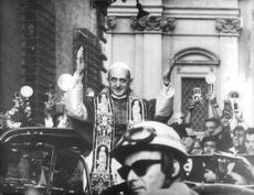 Pope Paul VI waves his hands to the cheering crowds during his parade.