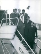King Saud with other people stepping downwards from airplane, 1964.