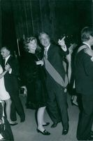 Eunice Kennedy Shriver and her husband US politician Sargent Shriver looking at something with smiling face at a party where couples are dancing
