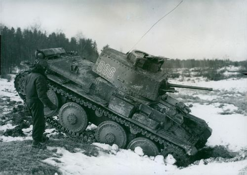 A soldier standing and looking the stuck tanks in the ice.1950