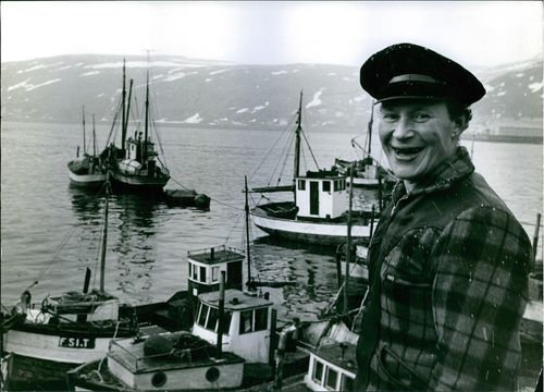 Close up of a a fisherman on the docks, looking towards the camera and smiling.