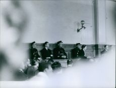 Men and some officers attending a court trial.