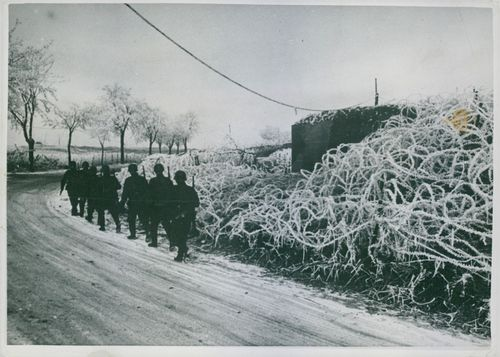 1940 Soldiers marching in single file in the road.