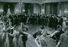 A photo of noble men and women dancing in a film.