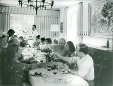 People at a table dining and drinking together.