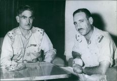 Abd al-Karim Qasim having discussion with another man and looking towards the camera.