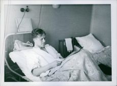 A man in the hospital reading a newspaper in Sweden during World War I, 1940.