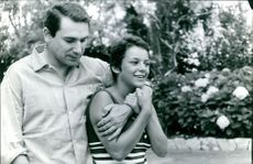 Robert Hossein putting hands on woman shoulder and smiling.
